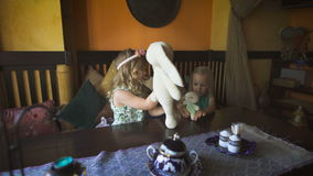 Two cute little blonde girls are playing in a cafe. Happy days. Two pretty little girls are playing with the stuffed animals. Little blondies are sitting on a stock video footage