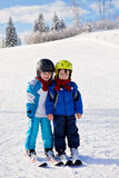 Two cute little boys, brothers, skiing on a sunny day Stock Photo