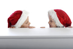 Two cute little boys looking from behind a table Royalty Free Stock Images