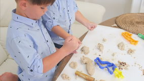 Two cute little boys playing with dough and learning how to bake stock video footage