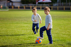 Two cute little boys, playing football Stock Image