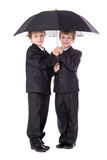 Two cute little boys twins in business suits with umbrella isola Stock Image