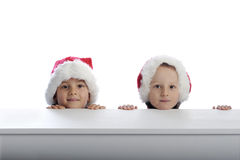 Two cute little boys with xmas hats Royalty Free Stock Image