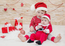Two cute little brother in Santa hats Stock Photos