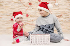 Two cute little brother in Santa hats Stock Photography
