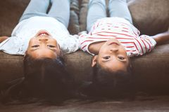 Two cute little child girls are lying on their backs on sofa. And playing together at home with fun and happiness royalty free stock photos