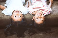 Two cute little child girls are lying on their backs on sofa. And playing together at home with fun and happiness stock photo