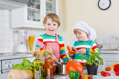 Two cute little children cooking italian soup and meal with fres Royalty Free Stock Photography