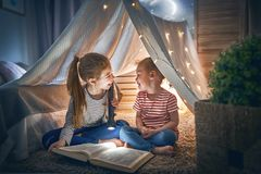 Children are reading a book. Two cute little children are reading a book with flashlights in tent. Happy girls playing at home. Funny lovely kids having fun in Stock Photo