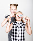 Two cute little girlfriend eating bright lollipops. Funny kids. Best friends pamper and posing Stock Photos