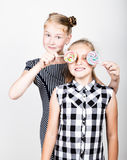 Two cute little girlfriend eating bright lollipops. Funny kids. Best friends pamper and posing Royalty Free Stock Photography