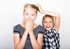 Two cute little girlfriend expressing different emotions. Funny kids. Best friends pamper and posing Stock Photography