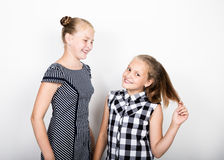Two cute little girlfriend expressing different emotions. Funny kids. Best friends pamper and posing Royalty Free Stock Photos
