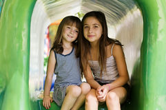Two cute little girls. Photo of two little girl's sitting down on a sunny day outside in a fun theme park royalty free stock photos