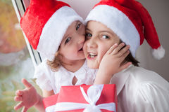 Two cute little girls with Christmas gifts. Little girl in Santa hat kissing older girl with Christmas gift Royalty Free Stock Photo