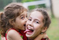 Two Happy little girls embracing and laughing at summer day. Two Cute little girls embracing and laughing at summer day in the park Stock Photo