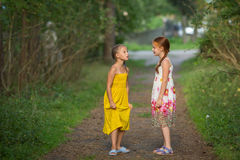 Two cute little girls friends in pine Park. Dialogue. Royalty Free Stock Photography