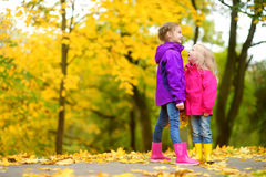 Two cute little girls having fun on beautiful autumn day. Happy children playing in autumn park. Kids gathering yellow fall foliag. E. Autumn activities for Royalty Free Stock Images