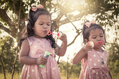 Two cute little girls having fun blowing bubbles in the park Stock Images