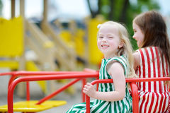 Two cute little girls having fun on a playground outdoors. In summer Royalty Free Stock Images