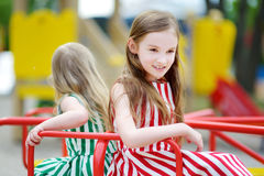 Two cute little girls having fun on a playground outdoors. In summer Royalty Free Stock Photo