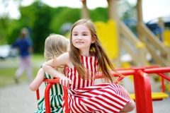 Two cute little girls having fun on a playground outdoors. In summer Stock Photo