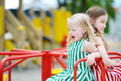 Two cute little girls having fun on a playground outdoors. In summer Stock Photography