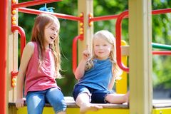 Two cute little girls having fun on a playground. Outdoors in summer Stock Images