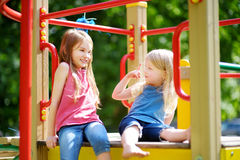 Two cute little girls having fun on a playground outdoors. In summer. Sport activities for kids Royalty Free Stock Photo