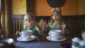 Two cute little girls are having tea in a cafe. Careless childhood. Two cute little girls in the dresses are having tea in a cozy cafe. Two beautiful blondies stock video footage