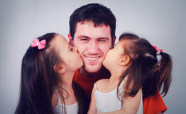Two cute little girls kissing his happy dad royalty free stock images