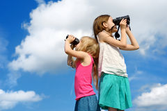 Two cute little girls looking through binoculars on sunny summer day Royalty Free Stock Image