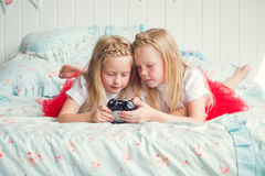 Two cute little girls lying on the bed Royalty Free Stock Photo