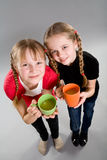 Two cute little girls with mugs Stock Photos