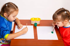 Two cute little girls are painting with gouache Royalty Free Stock Photography