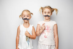 Two cute little girls with paper mustaches while posing against white background. Two cute little girls with paper mustaches while posing against white stock image