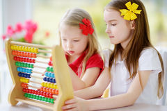 Two cute little girls playing with abacus at home. Big sister teaching her sibling to count. Royalty Free Stock Photo