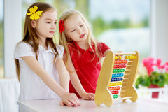 Two cute little girls playing with abacus at home. Big sister teaching her sibling to count. Stock Photos