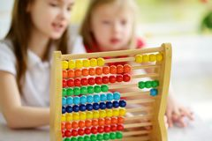 Two cute little girls playing with abacus at home. Big sister teaching her sibling to count. Smart child learning to count. Preschooler having fun with stock photography