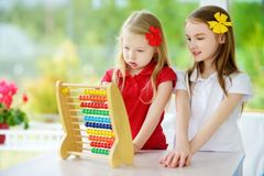 Two cute little girls playing with abacus at home. Big sister teaching her sibling to count. Smart child learning to count. Preschooler having fun with royalty free stock photo