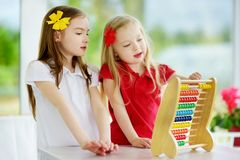Two cute little girls playing with abacus at home. Big sister teaching her sibling to count. Smart child learning to count. Preschooler having fun with stock photos