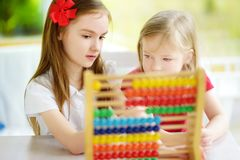 Two cute little girls playing with abacus at home. Big sister teaching her sibling to count. Smart child learning to count. Preschooler having fun with stock images