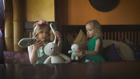 Two cute little girls are playing in a cafe stock video footage