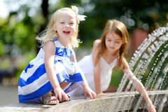 Two cute little girls playing with a city fountain on hot summer day Stock Photo