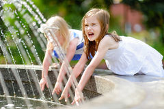 Two cute little girls playing with a city fountain on hot summer day Stock Photography