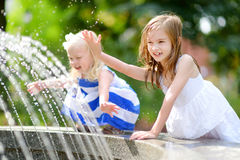 Two cute little girls playing with a city fountain on hot summer day Stock Image