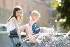 Two cute little girls playing with a city fountain Stock Photos