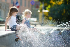 Two cute little girls playing with a city fountain Royalty Free Stock Photos