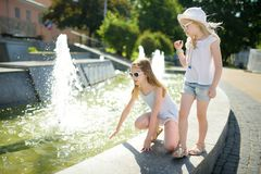 Two cute little girls playing by city fountain on hot and sunny summer day. Children having fun with water in summer royalty free stock photos