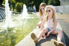 Two cute little girls playing by city fountain on hot and sunny summer day. Children having fun with water in summer stock image